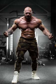 Bodybuilder en costume de père noël dans la salle de gym