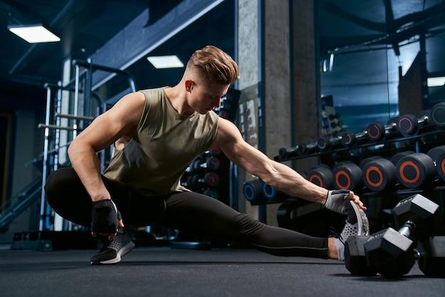 Bodybuilder étirant le haut du corps dans la salle de gym.