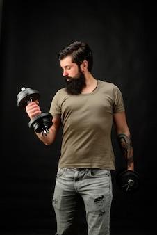 Bodybuilder faisant des biceps avec un homme de force d'haltères soulevant un homme athlétique sexy d'haltères montrant
