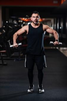Bodybuilder faisant de l'exercice pour les muscles de l'épaule, deltoïde avec haltère dans le gymnase