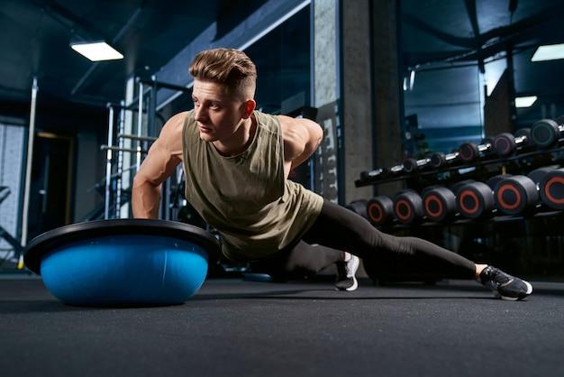 Bodybuilder faisant des pompes d'une part.