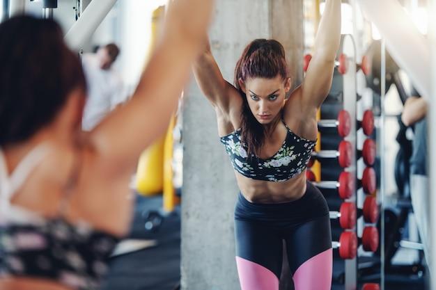 Bodybuilder femme caucasien attrayant avec queue de cheval et habillé en vêtements de sport dans la salle de gym. videz votre esprit de ne peut pas.
