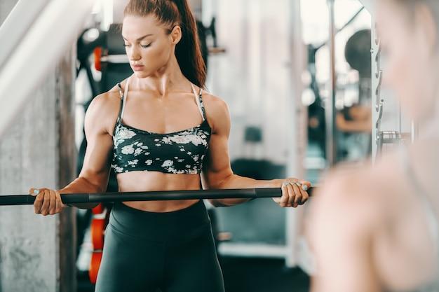 Bodybuilder femme caucasien attrayant avec queue de cheval soulevant des haltères en se tenant debout dans la salle de gym. willpower ne connaît aucun obstacle.
