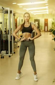 Bodybuilder femme jeune sport mince en vêtements de sport posant dans la salle de gym.