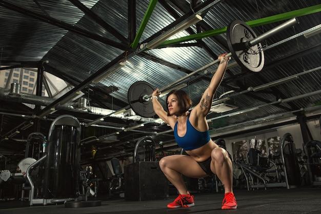 Bodybuilder femme séduisante faisant des squats lourds soulevant des haltères au gymnase
