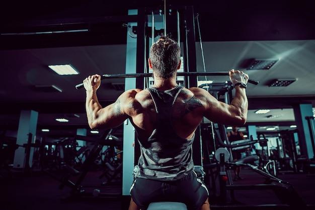 Bodybuilder fort faisant des exercices de poids lourd pour le dos sur la machine