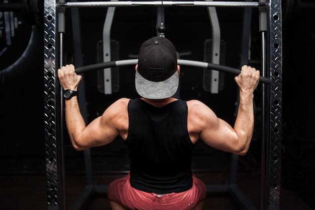 Bodybuilder fort faisant des exercices de poids lourd pour le dos sur la machine.