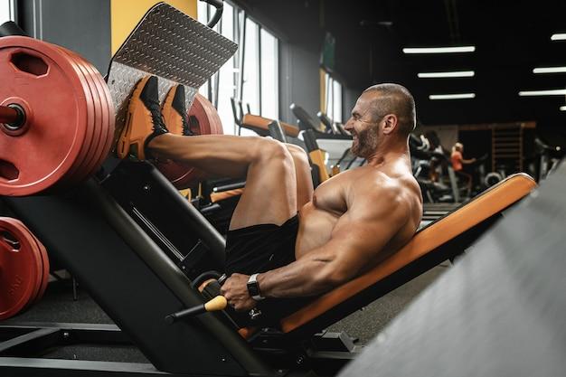 Bodybuilder fort et musclé faisant un exercice de presse à jambes assis dans une salle de sport