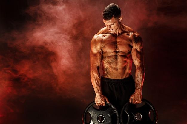 Bodybuilder avec des haltères dans ses bras