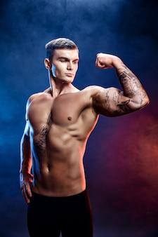 Bodybuilder homme athlétique puissance beau. corps musclé de remise en forme sur fond de fumée sombre. mâle parfait. bodybuilder génial, tatouage, pose.