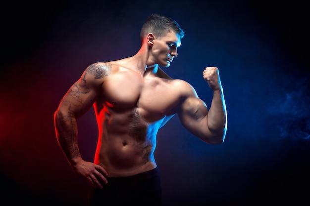 Bodybuilder homme athlétique puissance beau. corps musclé de remise en forme sur une scène de fumée sombre. mâle parfait. bodybuilder génial, tatouage, pose.