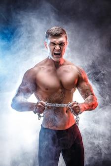 Bodybuilder homme athlétique puissance beau faire des exercices avec chaîne, déchirure. corps musclé de remise en forme sur fond sombre. mâle parfait. bodybuilder génial, tatouage, pose.
