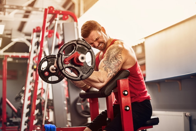 Bodybuilder homme faisant l'ensemble d'un exercice de barre dans une salle de sport. tir en temps réel