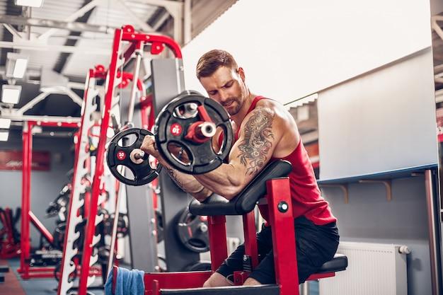 Bodybuilder homme faisant l'ensemble d'un exercice de barre dans une salle de sport.