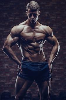 Bodybuilder homme fort, pompage des muscles abs