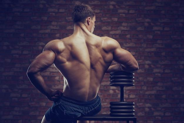 Bodybuilder homme fort, pompage des muscles du dos