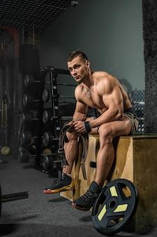 Le bodybuilder des hommes athlétiques forts brutaux s'entraîne dans la salle de gym