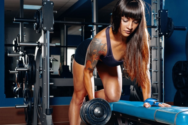 Bodybuilder jeune femme faisant des haltères tire dans un gymnase