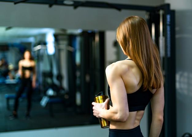 Bodybuilder de jeune femme en vêtements sportifs, debout devant le miroir avec ballon