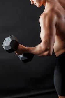 Bodybuilder mâle en short de remise en forme, faire des exercices avec bumbell