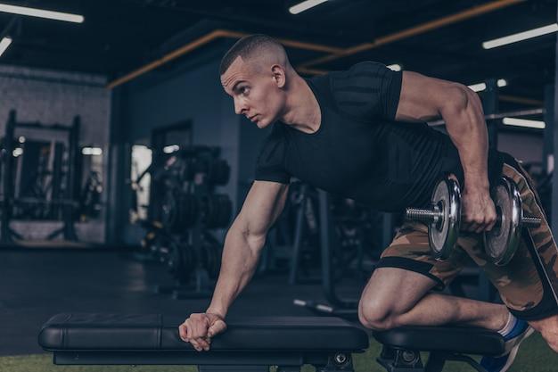 Bodybuilder mâle soulevant des haltères au gymnase