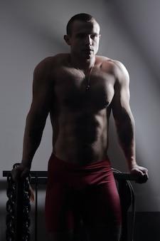 Bodybuilder masculin élégant avec une chaîne lourde debout dans la salle de gym.
