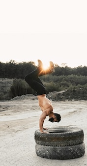Bodybuilder masculin professionnel faisant des exercices pour les bras sur les pneus à l'extérieur. jeune homme en masque noir s'entraînant régulièrement pour garder la forme du corps musclé.