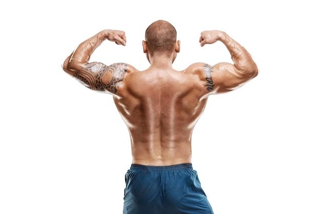 Bodybuilder masculin tatoué posant sur un mur blanc. entraînement de remise en forme