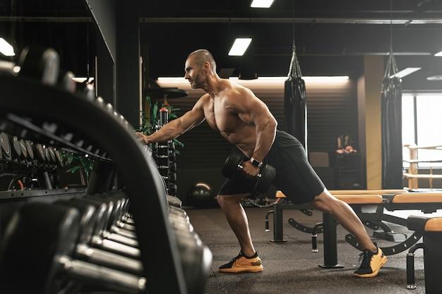 Bodybuilder massif faisant une rangée d'haltères à un bras pendant son entraînement dans une salle de sport