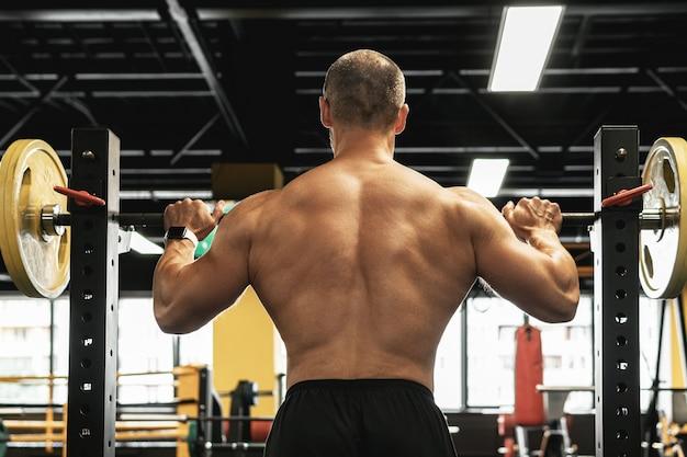 Bodybuilder massif pendant son entraînement avec une barre dans la salle de gym