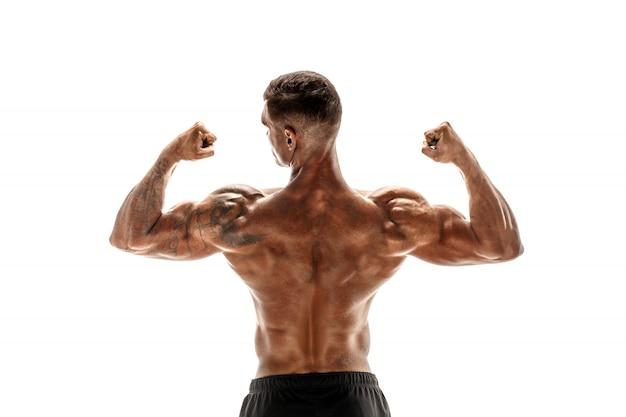 Bodybuilder montrant ses muscles du dos et du biceps isolés sur une scène blanche, entraîneur personnel