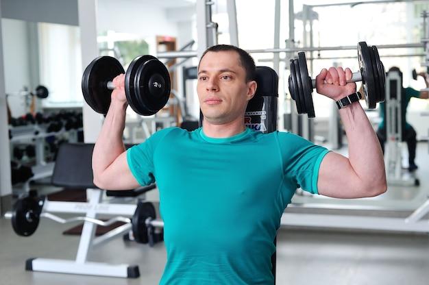 Bodybuilder musclé déchiré avec des haltères