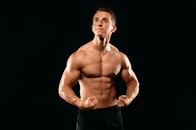 Bodybuilder musculaire ajustement sexy avec torse nu posant isolé sur noir