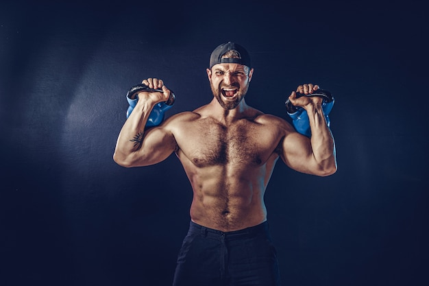 Bodybuilder musculaire barbu agressif faisant de l'exercice pour les muscles de l'épaule, deltoïde avec kettlebell. coup