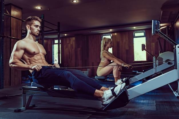 Bodybuilder musculaire dans la formation de vêtements de sport dos assis sur une machine d'exercice. vue latérale de l'homme avec un corps de musculation parfait dans une salle de sport dans une atmosphère sombre. concept de musculation, fitness.