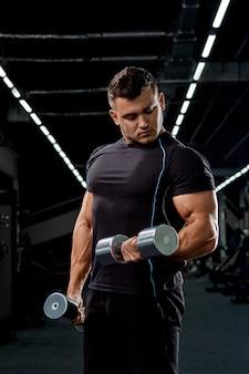 Bodybuilder musculaire, faire des exercices avec haltère dans la salle de gym. homme athlétique fort montre le corps, les muscles abdominaux, les biceps et les triceps.travaillez, prenez du poids, gonflez vos muscles avec des haltères.