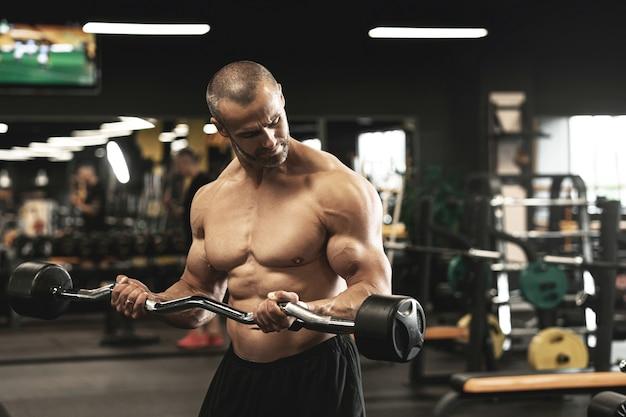 Bodybuilder musculaire faisant des boucles de biceps avec une barre pendant son entraînement dans le gymnase