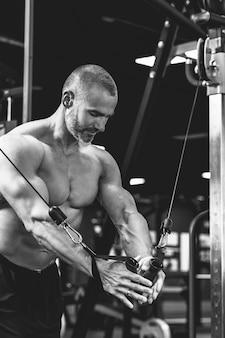 Bodybuilder musculaire faisant un exercice de croisement de câbles pour une poitrine pendant son entraînement dans la salle de sport