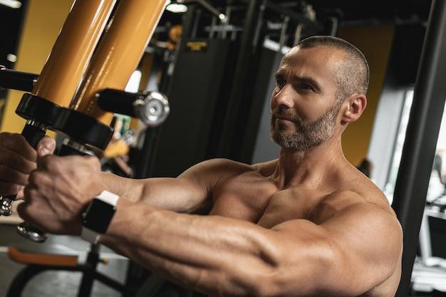 Bodybuilder musculaire faisant de l'exercice pec deck pour une poitrine pendant son entraînement dans la salle de gym