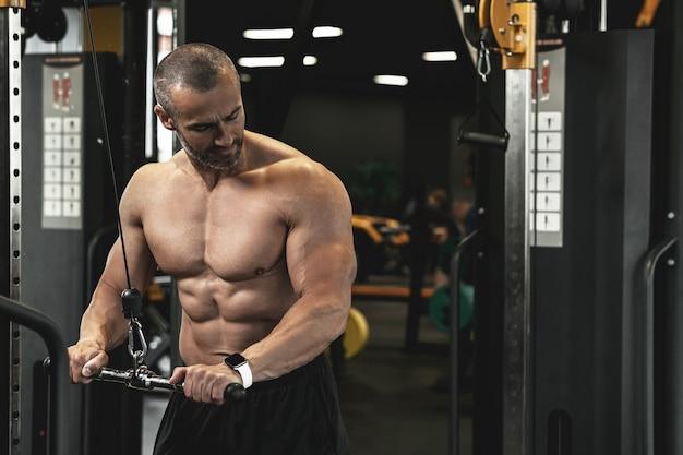 Bodybuilder musculaire faisant des pushdowns de triceps de câble pendant son entraînement dans le gymnase