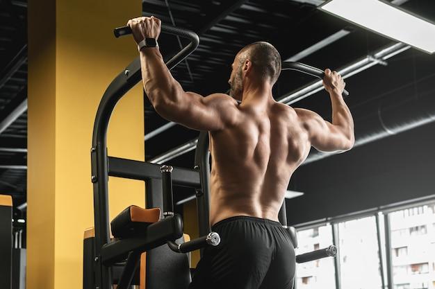 Bodybuilder musculaire faisant des tractions pendant son entraînement dans la salle de gym