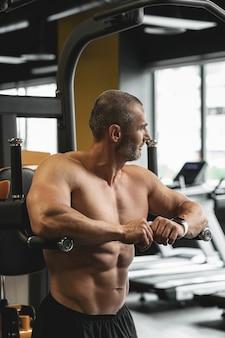 Bodybuilder musculaire faisant des trempettes pour les triceps et les muscles de la poitrine pendant son entraînement dans la salle de gym