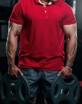 Bodybuilder en polo rouge détient des plaques d'une barre