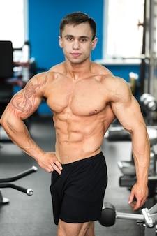 Bodybuilder posant dans la salle de gym