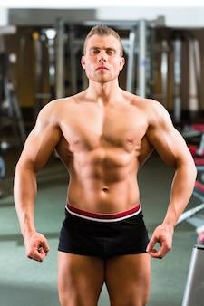 Bodybuilder posant dans une salle de sport