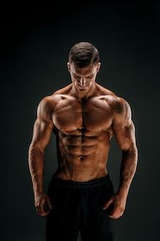 Bodybuilder posant fitness homme musclé sur scène sombre
