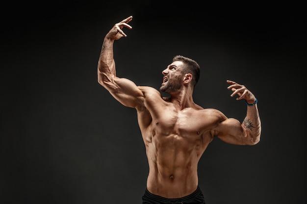 Bodybuilder posant. fitness musclé homme sur mur foncé.