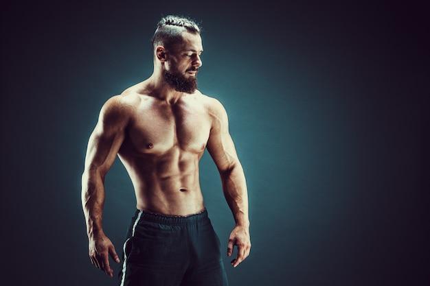 Bodybuilder posant. homme musclé de remise en forme sur fond sombre.