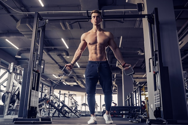 Bodybuilder de remise en forme musculaire faisant des exercices de poids lourds pour les muscles pectoraux sur machine avec câble dans la salle de gym