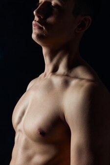 Bodybuilder sexy avec le torse nu sur la vue de côté de portrait de fond noir